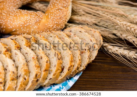 Sliced wholegrain bread with a sesame bagel displayed on a blue and white napkin with ears of ripe wheat, close up view - stock photo