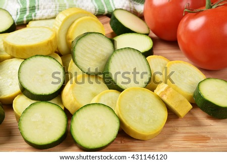 Sliced zucchini and yellow squash with fresh tomatoes - stock photo