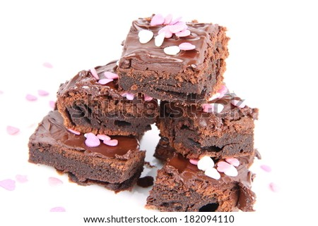 Slices of a brownie covered with chocolate and decorated with sugar hearts - stock photo