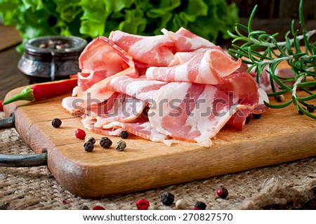 Slices of bacon on the wooden background - stock photo
