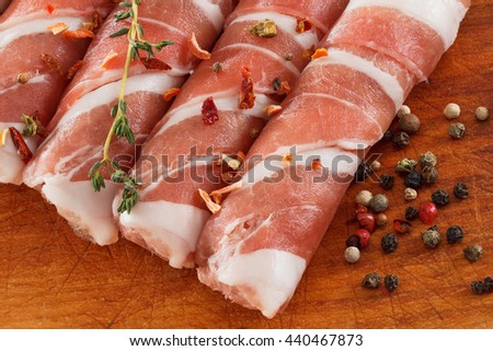 Slices of bacon roll closeup on cutting board with spices, cooking food