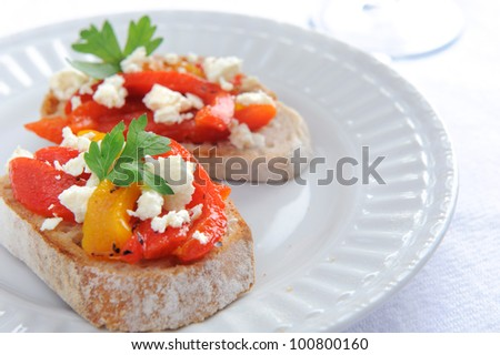 Slices of baguette topped with roasted red and yellow peppers with feta cheese - stock photo