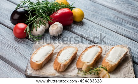 Slices of baguette with butter. Garlic and eggplant. Recipe of bruschetta. Basic ingredients for delicious snack. - stock photo