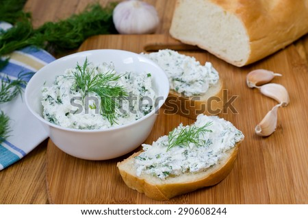 Slices of baguette with cottage cheese parsley, garlic on a cutting board. Curd sandwich in a bowl.