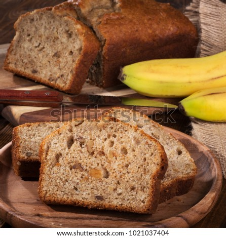 Slices of banana nut bread on a wooden plate with sliced loaf and bananas in background