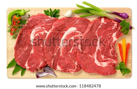 Slices of bovin on wooden board - stock photo