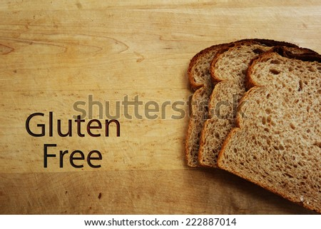 Slices of bread and Gluten Free text on a cutting board                                - stock photo