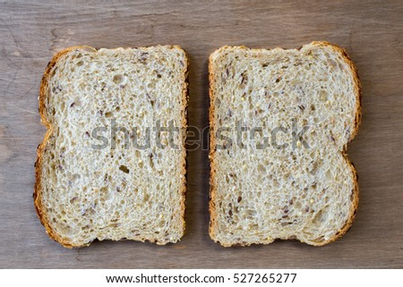 Slices of bread from above with wooden background.