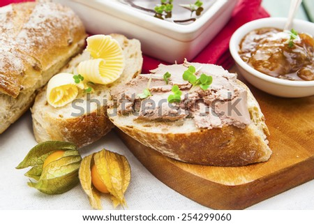 Slices of bread, pate and butter on wooden cutting board with dish of pate, knife, chutney and physalis over white cloth  - stock photo