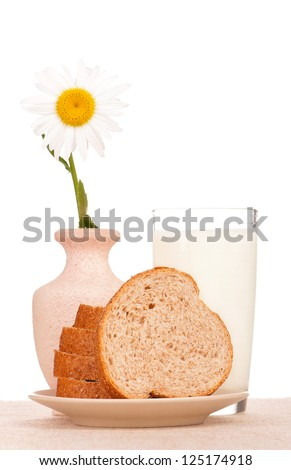 Slices of bread with bran and a glass with milk on a burlap over white - stock photo
