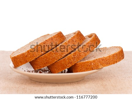 Slices of bread with bran on a plate on burlap - stock photo