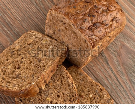 Slices of brown bread on a wooden table - stock photo