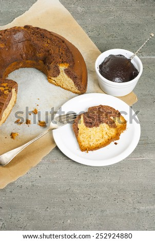 slices of bundt cake with chocolate cream on old wooden table