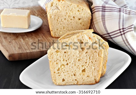 Slices of cheddar cheese bread in front of loaf and a piece of cheddar. - stock photo
