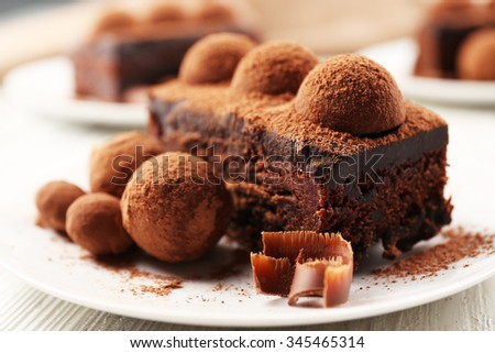 Slices of chocolate cake with a truffle on plate closeup - stock photo
