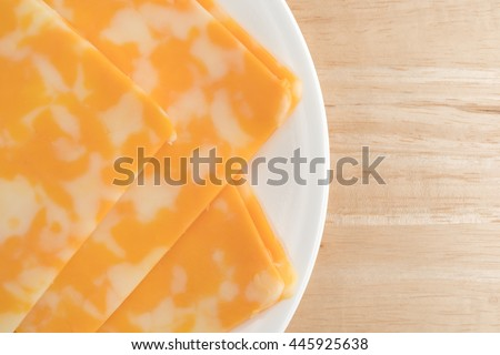 Slices of Colby-Jack cheese on a white plate atop a wood table.