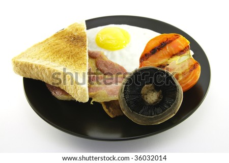 Slices of crispy pork bacon with half a grilled tomato a fried egg, mushroom and a slice of lightly toasted bread on a black round plate with a white background