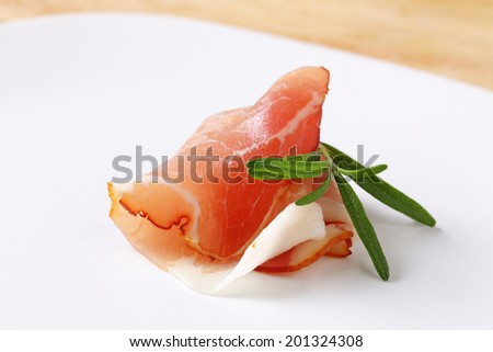 Slices of delicious prosciutto with rosemary - stock photo