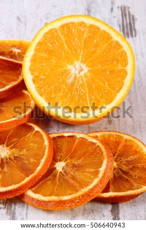 Slices of dried and portion of fresh orange lying on old rustic wooden background, healthy food