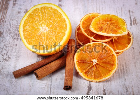 Slices of dried and portion of fresh orange with cinnamon sticks on old rustic wooden background, healthy food