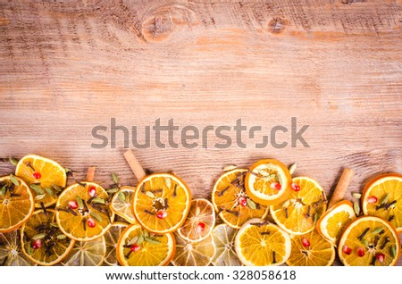 Slices of dried orange, lemon, cinnamon, cloves, cardamom and pine cone. Christmas and New Year decoration. Free space for text. - stock photo