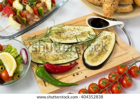 Slices of eggplant on wooden cutting board - stock photo