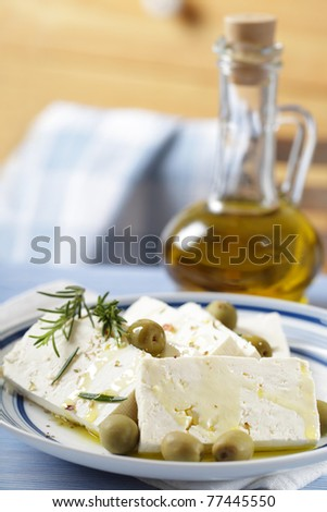 Slices of feta cheese with green olives and olive oil