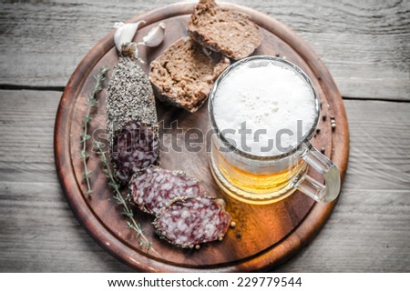 Slices of french Saucisson sausage with glass of beer - stock photo