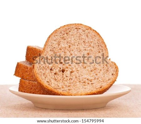 Slices of fresh bread with bran on a saucer on a burlap over white background - stock photo