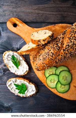 Slices of fresh cucumber and baguette on beige cutting board and sandwich with cream cheese and parsley on rustic wooden background. Top view - stock photo