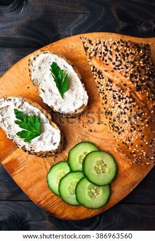 Slices of fresh cucumber, baguette and sandwich with cream cheese and parsley on wooden cutting board - stock photo