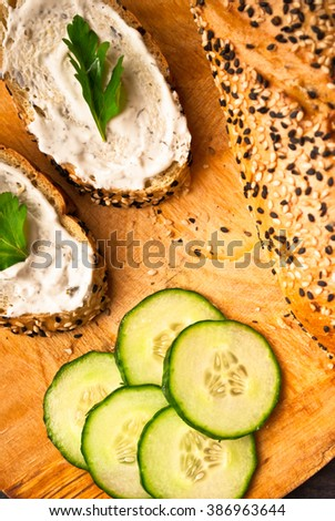 Slices of fresh cucumber, part of baguette and sandwich with cream cheese and parsley on rustic wooden background. Close up - stock photo