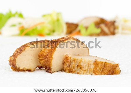 Slices of fresh grilled chicken on white kitchen paper towel with salad background - stock photo