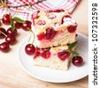Slices of fresh iced sponge cake with cherries - stock photo