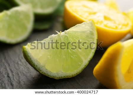 Slices of fresh lemon and lime with green leaves on table closeup