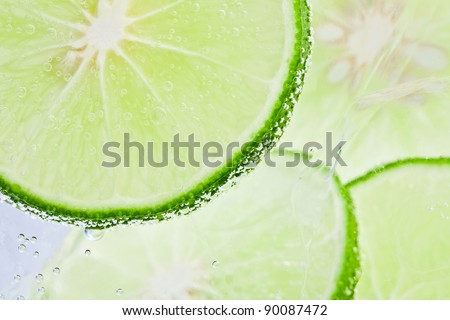 Slices of fresh lime floating in sparkling water - stock photo