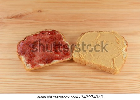 Slices of fresh oat and linseed bread with jelly and peanut butter on a wooden kitchen table - stock photo