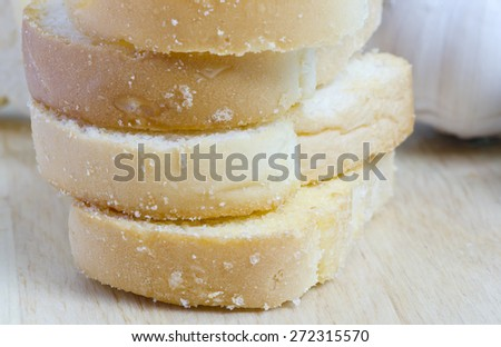 Slices of freshly baked garlic bread  with butter and sugar. Macro with extremely shallow dof. - stock photo