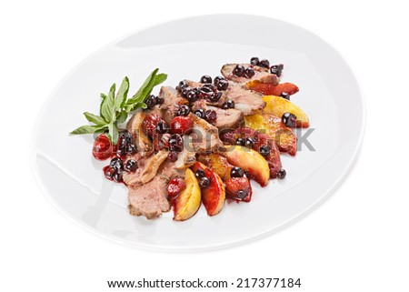 Slices of  fried meat on a plate with fruit  and berries. - stock photo