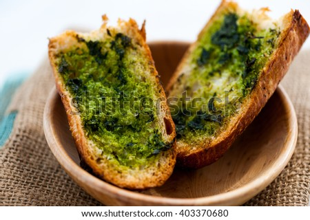 Slices of garlic bread with wild young garlic leaves