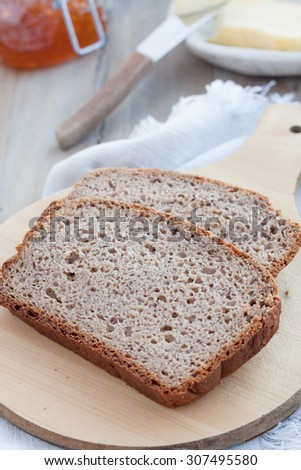slices of gluten free bread made with psyllium husk powder on chopping board - stock photo