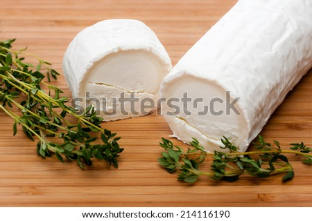 Slices of Goat cheese seasoned with Thyme. Displayed on a cutting board of Bamboo. - stock photo