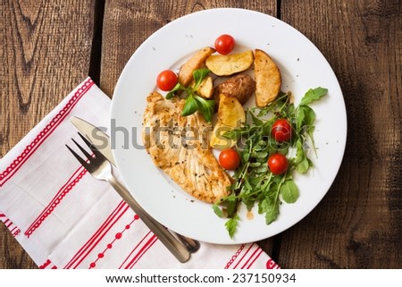 Slices of grilled chicken steak with potatoes and vegetables. Top view. - stock photo