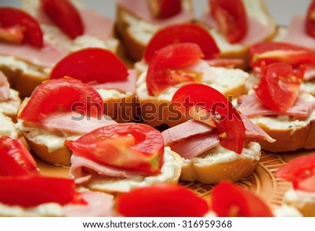 Slices of ham and cheese with tomatoes - stock photo