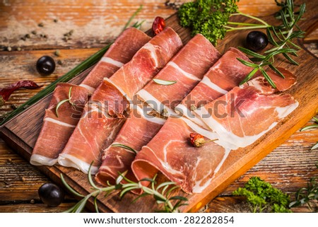 Slices of ham and herbs on a wooden table - stock photo