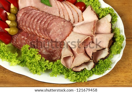 Slices of ham, cutting sausage and cured meat. Polish cold starter - stock photo