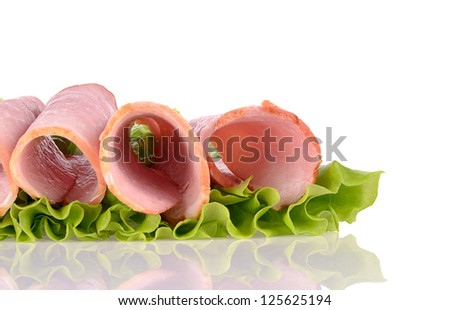 Slices of ham on green salad, isolated on a white background