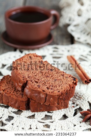 Slices of homemade chocolate cake with figs and a cup of coffee on wooden table, selective focus
