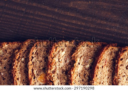 Slices of homemade whole grain bread on the dark wooden beckground, close up - stock photo