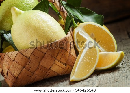 Slices of lemon and cut lemons with leaves in a wicker basket on an old wooden table in rustic style, selective focus - stock photo